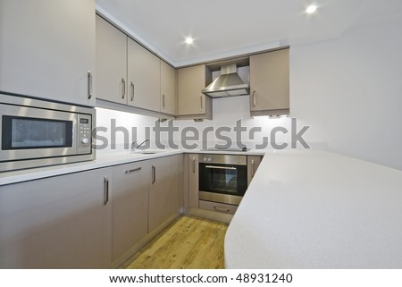 modern luxury kitchen with limestone worktop and built in electric appliances - stock photo