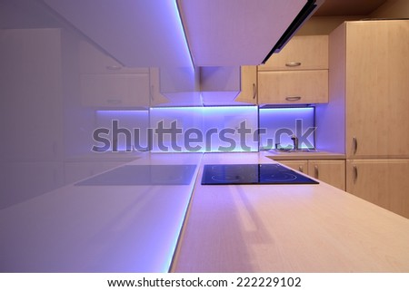 Modern luxury kitchen with purple LED lighting - stock photo