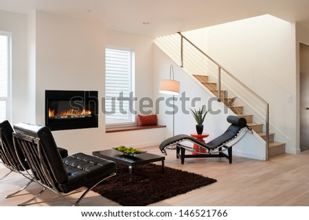 Modern Luxury Living Room/Horizontal shot of a modern living room in an upscale home with lounge chairs, and a view of stairs and fireplace. - stock photo