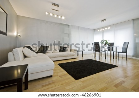 modern luxury living room with white leather corner sofa and round dining table - stock photo