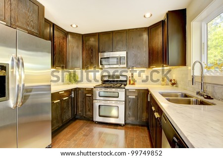 Modern luxury new dark brown and white kitchen with stainless steal appliances. - stock photo