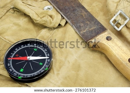 Modern Magnetic Compass And Old Rust Knife On The Green Weathered Backpack Background - stock photo
