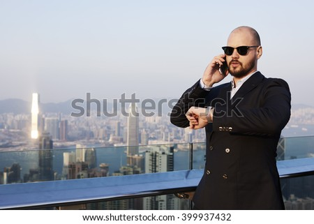 Modern man entrepreneur with luxury look is checking time,while having cell telephone conversation with partner during business trip in China. Rich male is talking on mobile phone on a skyscraper roof - stock photo