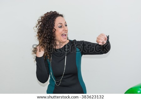 Modern mature woman, happy and smiling,  use the smartwacth. She has long curly hair and blacks, with green eyes. Cheerful and smiling. - stock photo