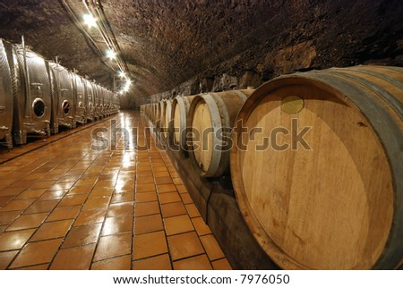 Modern metal and old fashioned wooden wine barrels in a cave