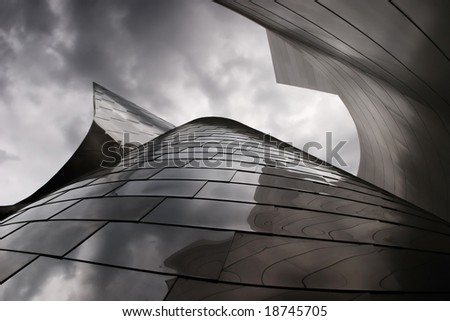 modern metal building with a cloudy sky above - stock photo