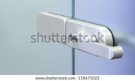Modern metal office door handle on a glass door - stock photo