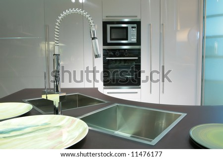 modern metallic sink with graceful tap and plate on the super-modern kitchen - stock photo
