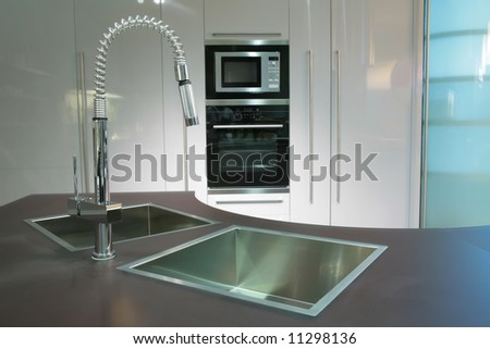 modern metallic sink with graceful tap on the super-modern kitchen - stock photo