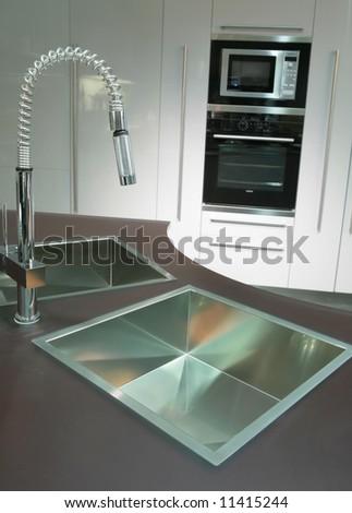 modern metallic sink with graceful tap on the super-modern kitchen - stock photo