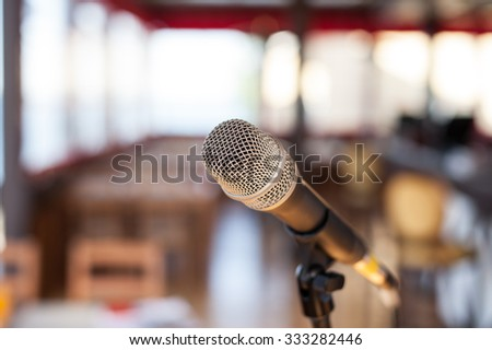 modern Microphone in concert hall or conference room with windows and defocused bokeh lights in background. One alone object in Empty space inside against table and chair