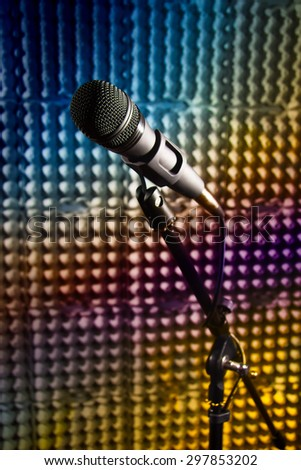 Modern microphone on a stand, recording studio, microphone picture, sound wall, microphone stand, mesh wire, close-up shot, vertical image, images in bright colors. - stock photo