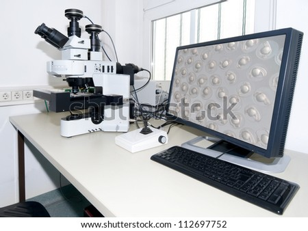 Modern microscope equipped with digital camera, computer and monitor - stock photo