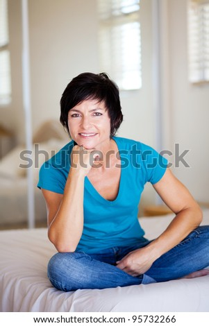 modern middle aged woman sitting on bed relaxing - stock photo