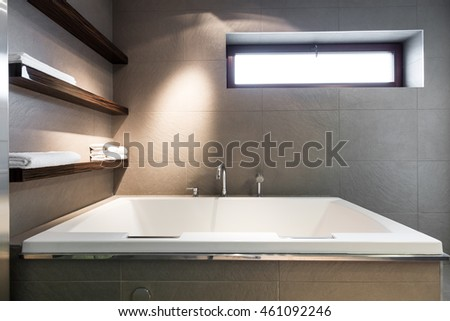 Modern, minimalist bathroom with a large, square bath, towel shelves and a rectangular window