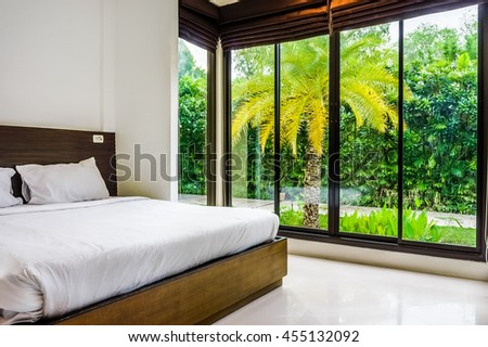 Modern minimalist bed room with wide glass windows. It design to give scenic view of natural outdoor garden. - stock photo