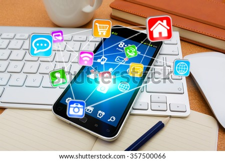 Modern mobile phone in office with icons flying over - stock photo