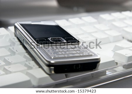 Modern mobile phone on white computer keyboard. Focus on center phone button.