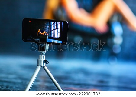Modern mobile phone shooting video with model. - stock photo