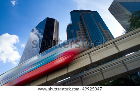 Modern monorail train with office buildings in the background