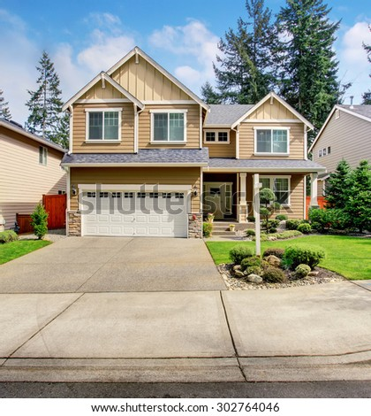 Modern northwest home with tan exterior, garage, and well kept lawn. - stock photo