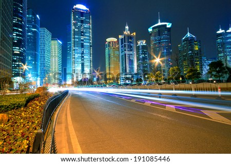 Modern office building background of car night with light trails in Shanghai - stock photo