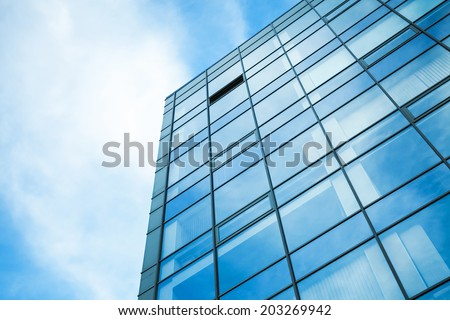 Modern office building wall made of steel and glass with blue sky - stock photo