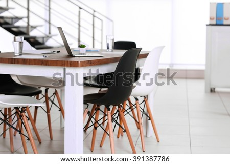 Modern office. Furniture set with table and chairs. Laptop on the table - stock photo