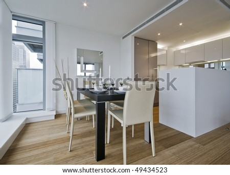 modern open plan kitchen with dining table and setup - stock photo