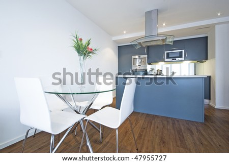 Modern open plan living area with fully fitted kitchen and a dining table for four - stock photo