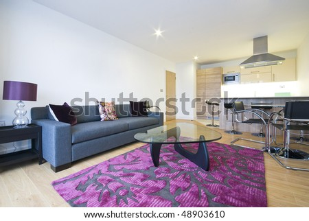 Modern open plan living area with fully fitted kitchen and dining table for four - stock photo