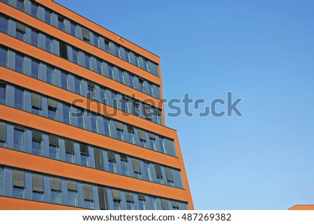 Modern orange building with blue windows