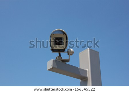 Modern outdoor surveillance camera aiming straight at the beholder.