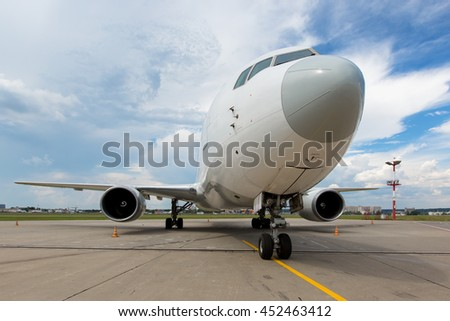 Modern passenger airplane on the airport runaway. Front view of aircraft with bright blue sky and cumulus clouds at the background. - stock photo
