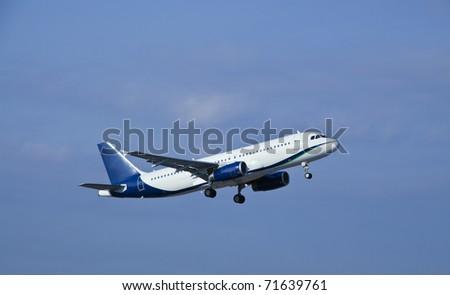 Modern passenger jet airplane at take off - stock photo
