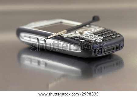 Modern PDA on shiny surface with shallow dof (focus on keypad) - stock photo