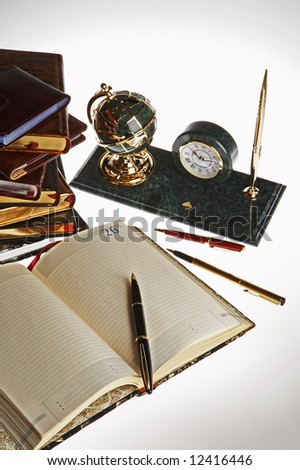 Modern pens, the notebook, books and a desk set with clock - stock photo