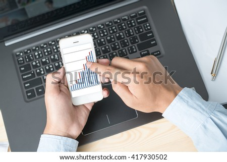Modern people doing business, graphs and charts being demonstrated on the screen of a touch-pad - stock photo