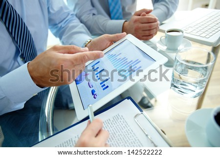 Modern people doing business, graphs and charts being demonstrated on the screen of a touchpad - stock photo