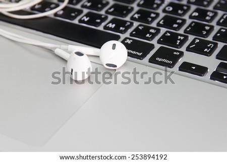 modern phone with earphones laying on laptop keyboard - stock photo