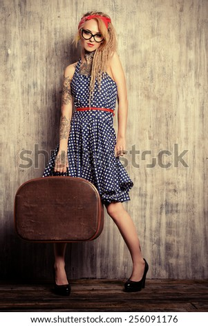 Modern pin-up girl in old-fashioned polka-dot dress and modern hairstyle dreadlocks holding old suitcase. Fashion shot. Mixture of styles.