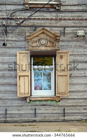 Modern plastic windows framed by old wooden architraves and shutters. Irkutsk street, Russia