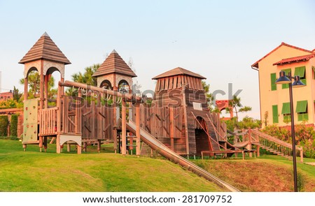 modern playground made of wood on green lawn in the public park - stock photo