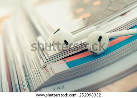 Modern portable audio earphones on magazines - stock photo