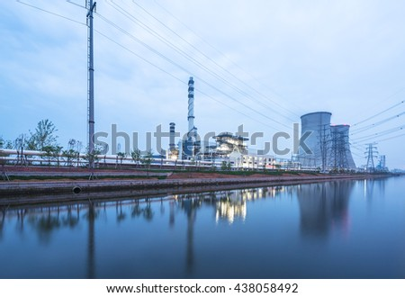 modern power station near river at twilight