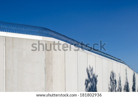 Modern prison wall against clear blue sky. Dark tree shadows on the wall. - stock photo