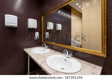 Modern Public bathroom with ceramic walls - stock photo