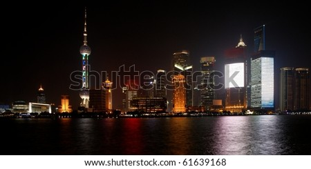 Modern Pudong district in Shanghai at night (logos removed) - stock photo