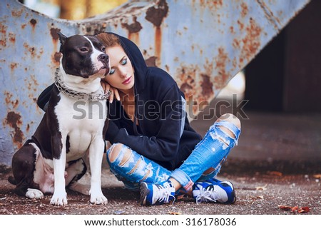 modern punk fashion, portrait of a beautiful model posing with American staffordshire terrier over street background