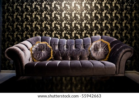 Modern purple sofa with two cushions in front of beautiful wallpaper. - stock photo